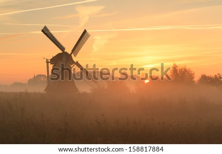 Traditional Dutch windmill at a foggy sunrise in the countryside