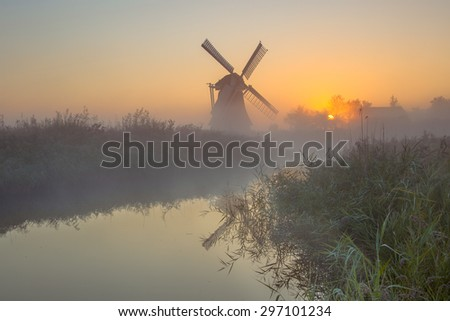 Traditional dutch Windmill in marshy countryside on a foggy morning in september