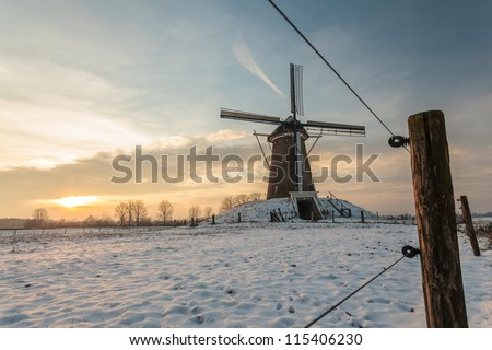 Traditional Dutch windmill in winter during sunset with wooden fence in front - stock photo