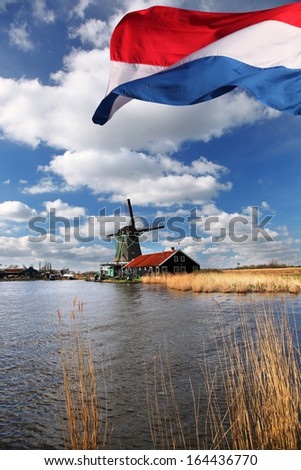 Traditional Dutch windmills near the Amsterdam with flag of  Holland - stock photo