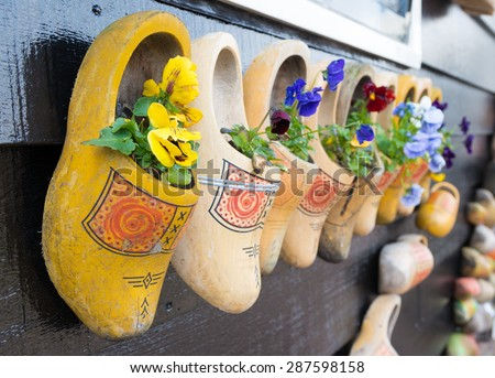 traditional dutch wooden shoes hanging on a wall as decoration - stock photo