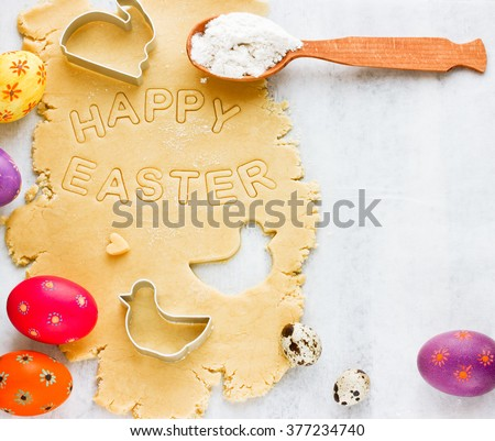 Traditional Easter baking background. Shortcrust pastry for holiday cookies, colorful eggs, biscuit cutters on white wooden table, top view with copy space - stock photo