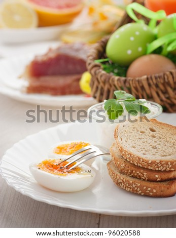 Traditional Easter breakfast. Table setting with Boiled eggs with ham, cottage cheese and Easter decorations - stock photo