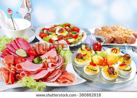 traditional easter breakfast with stuffed eggs,ham and cured meat platter,salad and white sausage with onion - stock photo