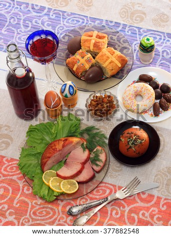 Traditional easter dinner set with sliced meat with lemon and herbs, bread, handmade colored eggs, chocolates, raisins, easter cake and wine on colorful tablecloth, close up - stock photo
