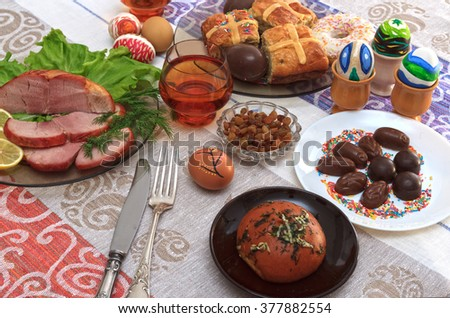 Traditional easter dinner set with sliced meat with lemon and herbs, bread, handmade colored eggs, chocolates, raisins, easter cake and glasses of juice on colorful tablecloth, horizontal view - stock photo