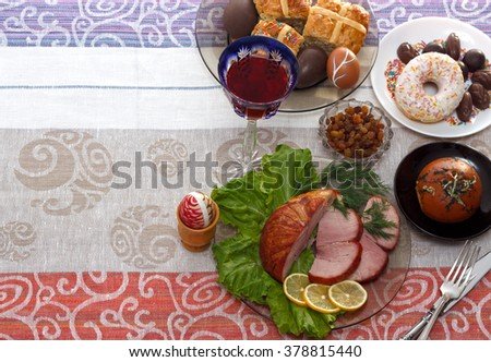 Traditional easter dinner set with sliced meat with lemon and herbs, bread, handmade colored eggs, chocolates, raisins, easter cake and wine on colorful tablecloth with copy space, horizontal top view - stock photo