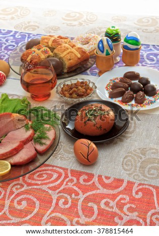 Traditional easter dinner set with sliced meat with lemon and herbs, bread, handmade colored eggs, chocolates, raisins, easter cake and glasses of juice on colorful tablecloth with copy space - stock photo