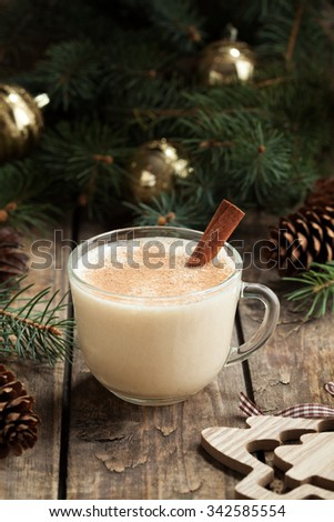 Traditional eggnog homemade christmas non alcohol winter drink in glass cup with cinnamon stick on vintage wooden table. Xmas fur decorations. Rustic style. - stock photo
