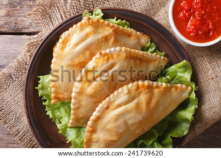 Traditional empanadas on a plate and sauce closeup. horizontal view from above, rustic style  - stock photo
