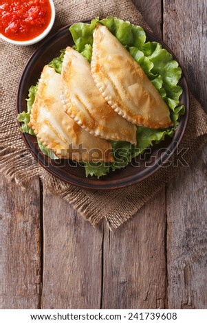 Traditional empanadas on a plate and sauce. vertical view from above, rustic style  - stock photo