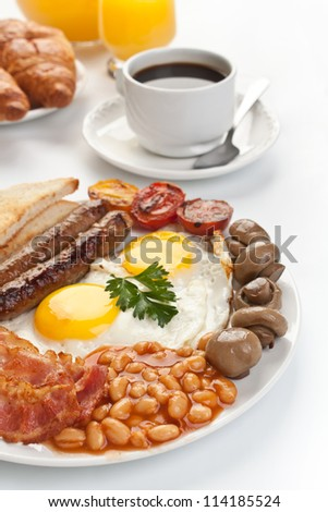 Traditional English breakfast - plate with fried eggs, sausages, beans, mushrooms and bacon, cup of fresh coffee, croissants and orange juice on white background - stock photo