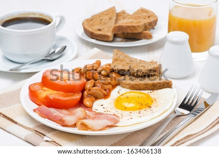 Traditional English breakfast with fried eggs, bacon and beans, horizontal - stock photo