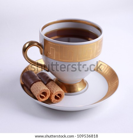 Traditional English tea - white and gold china cup of tea with cookies - stock photo