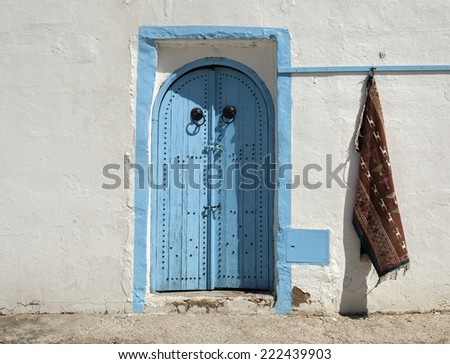 Traditional entrance door blue colour and carpet,  Tunisia