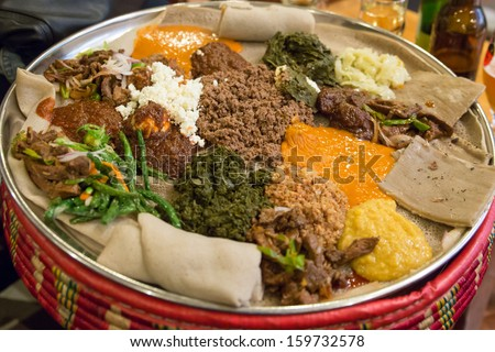 Traditional Ethiopian Food, Several types of stew and meat served on Injera - stock photo