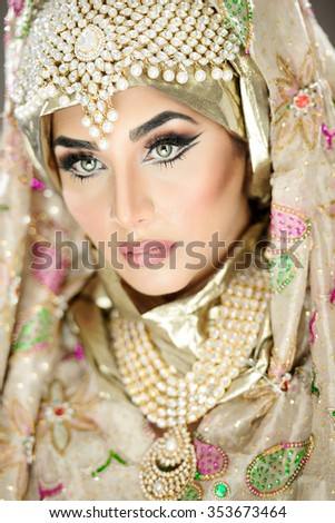 Traditional ethnic bride in costume with heavy jewellery and hijab - stock photo
