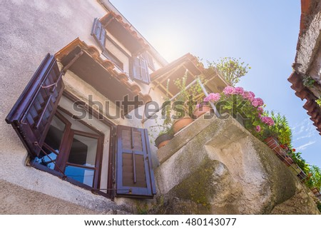 Traditional European Mediterranean architectural style in the streets and residential houses, yard, porches, stairs, shutters in the noon sunbeam, surrounded by vine, hydrangea and palm at summertime.