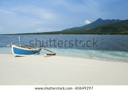 traditional filipino banka outrigger fishing boat on white sand beach of camiguin island near mindanao in the philippines - stock photo