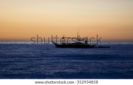 Traditional filipino outrigger on the ocean during a vivid sunset - stock photo