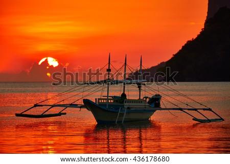 Traditional filippino boat at El Nido bay in sunset lights. Palawan island, Philippines - stock photo