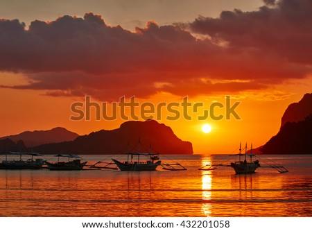 Traditional filippino boats at El Nido bay in sunset lights. Palawan island, Philippines - stock photo
