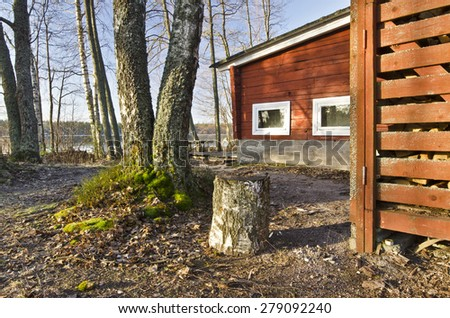 Traditional Finish Sauna colored in red is in the border of lake in the forest. This typical wooden construction in Finland has a dry firewood storage place, Rajamaki, Saaksjarvi lake in spring - stock photo