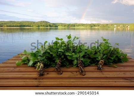 Traditional Finnish bath whisks made out of fresh birch leaves and twigs on a wet jetty by the lake on Midsummer Eve in Nokia, Finland with rainbow visible in the horizon. - stock photo