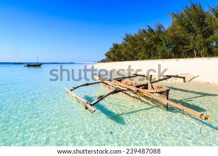 Traditional fisherman boat lying near the beach in clear water near tropical island - stock photo