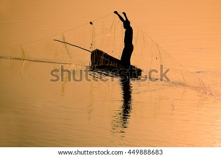 Traditional fisherman casting a net at sunset