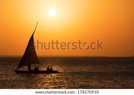 Traditional Fisherman Dhow Boat  during sunset, Zanzibar, Tanzania - stock photo