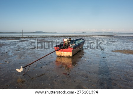Traditional fishing boat on sandy beach in low tide, Thailand - stock photo