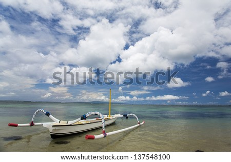 Traditional fishing boats on a beach in Sanur on Bali - stock photo