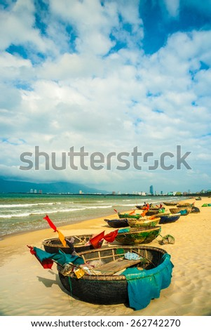Traditional fishing boats on the beach of Da Nang city, the cityscape and Son Tra peninsulain are visible in distance. Vietnam.