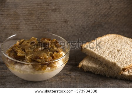 """Traditional food mashed beans """"iahnie"""" with fried onions on top and fresh bread  - stock photo"""