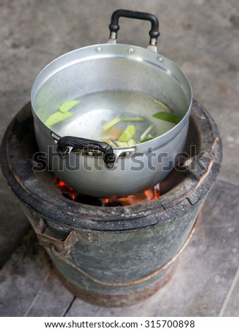 traditional food preparation in a tin pot on the fireplace in a bucket