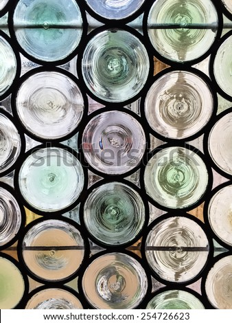 Traditional French chateau window made of circular tinted glass forming an interesting pattern and texture suitable for backgrounds or wallpapers