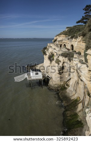 traditional french fisherman's wooden hut at the bottom of the limestone cliff in the estuary of Gironde, Meschers-sur-Gironde