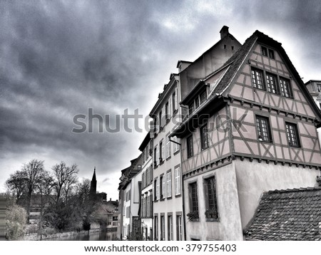 Traditional french houses in Alsace with a cloudy grey sky in background