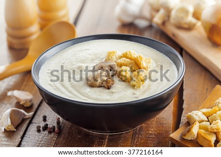 Traditional French mushroom cream soup in a bowl served for lunch, food cooking