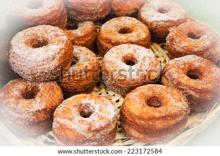 Traditional French puff doughnuts pastries sprinkled with sugar for sale at food market in Paris. - stock photo