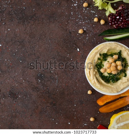 Traditional fresh hummus served with green spicy olive oil and vegetables.