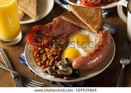 Traditional Full English Breakfast with Eggs, Bacon, Sausage, and Baked Beans - stock photo