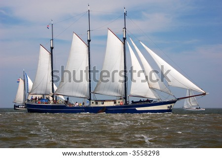 Traditional gaffrigged 3 masted dutch sailing barge, with other boats in the background. - stock photo
