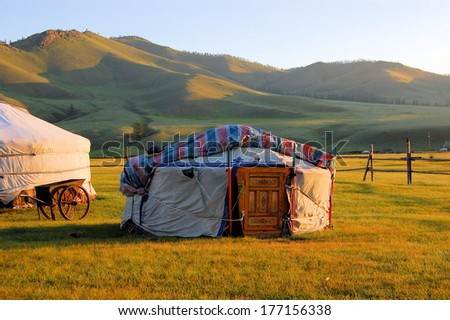 Traditional ger tent home of Mongolian nomads on the grass plains of the steppe with colorful rolling hills - stock photo