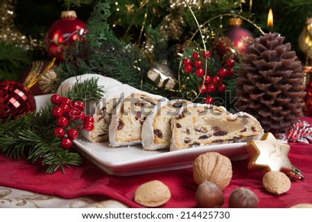 Traditional German Christmas cake - Cranberry Stollen, Christmas tree, ornaments, and candles.  - stock photo