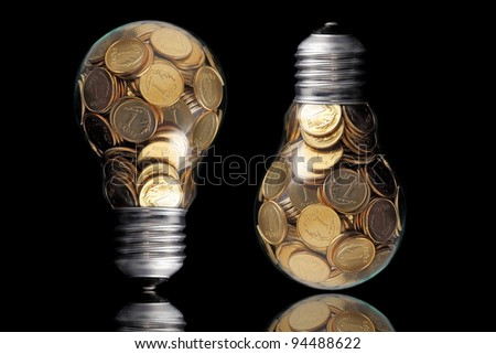 Traditional glass bulb with many golden coins on black