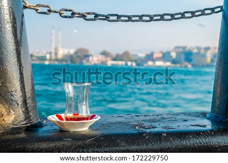 Traditional glass of Turkish tea on the cruise over the bosphorus sea - stock photo