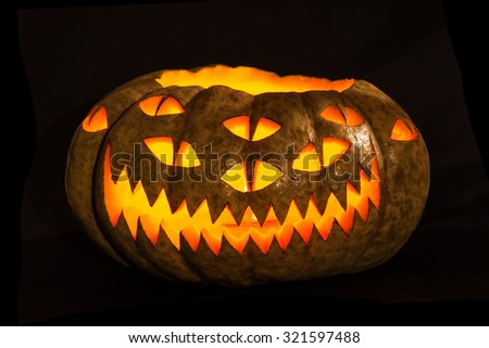Traditional glowing Halloween Jack-o-Lantern with carved unusual scary face with lots of eyes. Halloween pumpkin isolated over black.