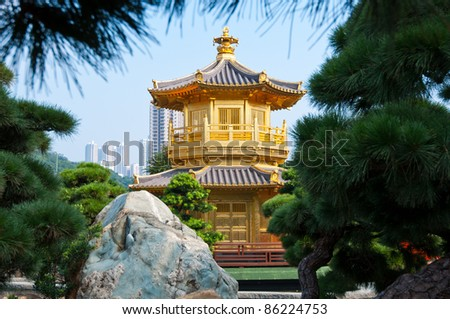 traditional golden chinese temple with coniferous trees around - stock photo